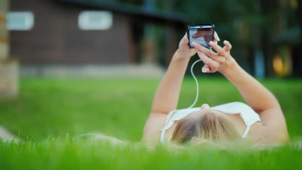 Thumbnail for A Young Girl Is Lying on Her Back on the Lawn, Enjoying a Smartphone