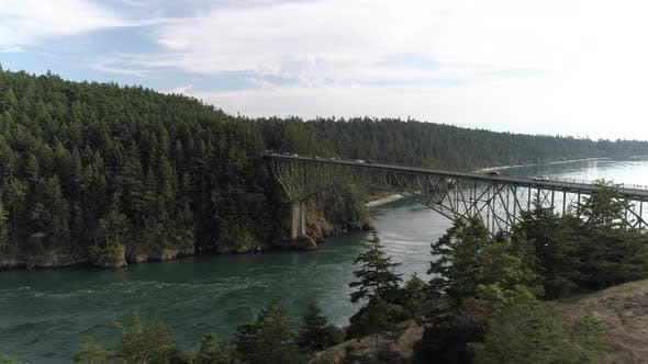 Thumbnail for Forest Trees Drone Reveal Of Cars In Commute On High Ocean Bridge In Pacific Northwest