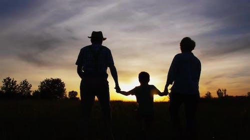Grandparents and Little Grandson Walking at Sunset