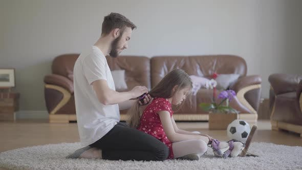 Thumbnail for Young Bearded Father Brushing the Hair of His Little Girl While the Child Combing the Tail of Her