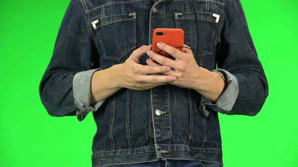 Thumbnail for Guy Texting with Red Smartphone While Walking, Close Up. Green Screen