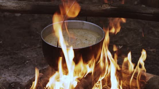 Old Retro Camp Saucepan Boiled Water For Soup Preparation On A Fire In Forest. Flame Fire Bonfire At