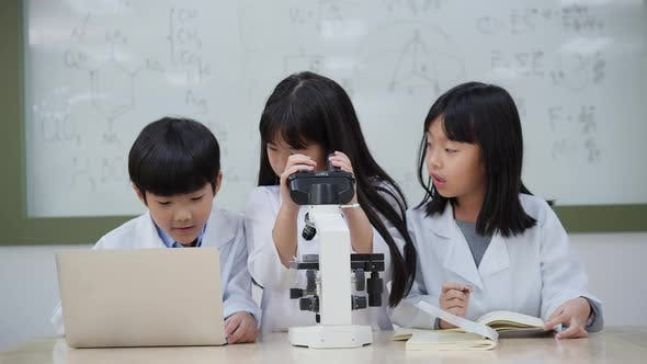 Students kids looking microscope and study in laboratory