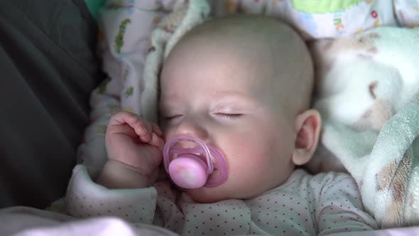 A Baby Is Sleeping with a Pacifier in Its Mouth in a Stroller. Face Close Up
