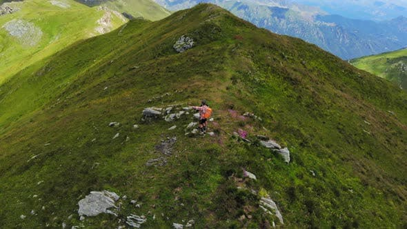 Thumbnail for Aerial: couple backpackers hiking on mountain top Summer adventures on the Alps