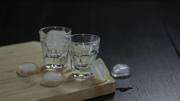 Thumbnail for Vodka in Shot Glasses on Rustic Wood Board. Adding Ice Cubes