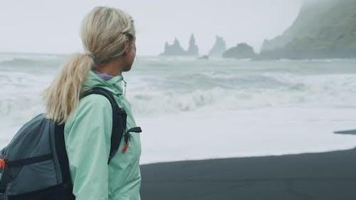 Woman with a Green Raincoat Walking on a Black Sand Beach Enjoying View to Reynisfjara Sea Stack