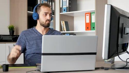 Designer Drawing on Digital Tablet setzt Kopfhörer auf