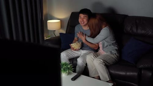 shocked young couple is watching horror movie TV on sofa at night