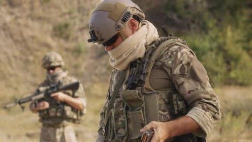 Male Soldier Reloading Firearm During War