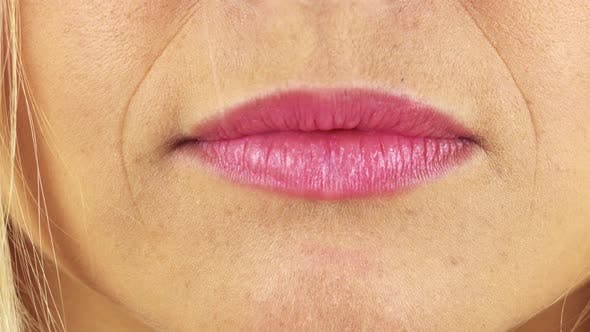 Thumbnail for Closeup on a Woman's Full Lips Pressed Into a Thin Line