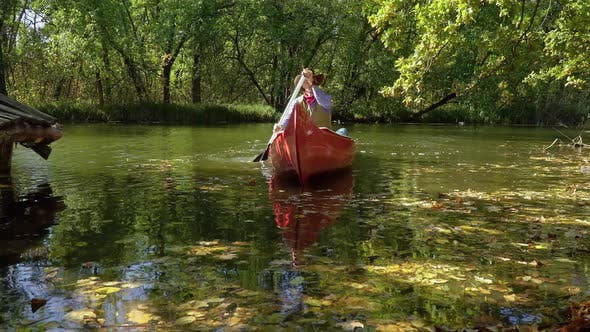 Thumbnail for Cowboy in a Canoe Floats on the River in the Forest