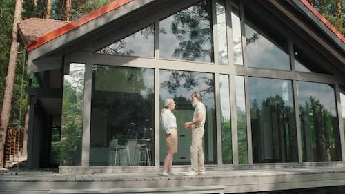 Upper-Class Senior People Talking on Porch of Modern House