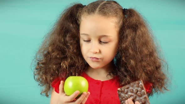 Child Makes a Choice Between of Holding a Green Apple and Chocolate Cute Child on Turquoise