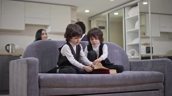 Wide Shot of Positive Friendly Siblings Sitting on Couch Reading Book Talking Smiling