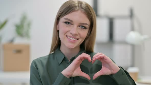 Portrait of Young Woman Making Heart Sign By Hand