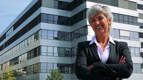 Thumbnail for Business Middle Age Woman Smiles To Camera with Crossed Arms - Company Building in the Background