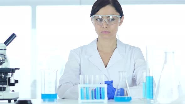 Thumbnail for Young Female Scientist Sitting in Laboratory