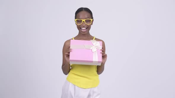 Thumbnail for Happy Young Beautiful African Woman Holding Gift Box