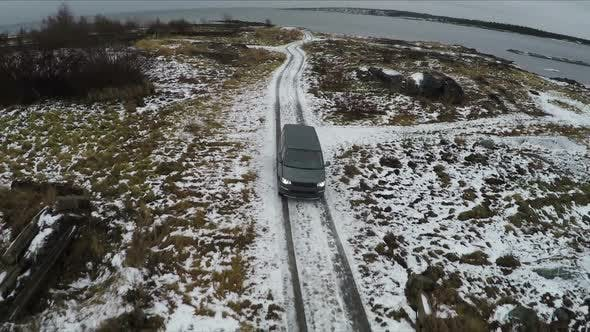 Thumbnail for Aerial View of Car Driving Away From Shore in Winter