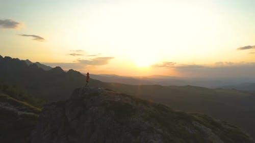 Adventurous Man Climbing Mountain Peak at Sunset