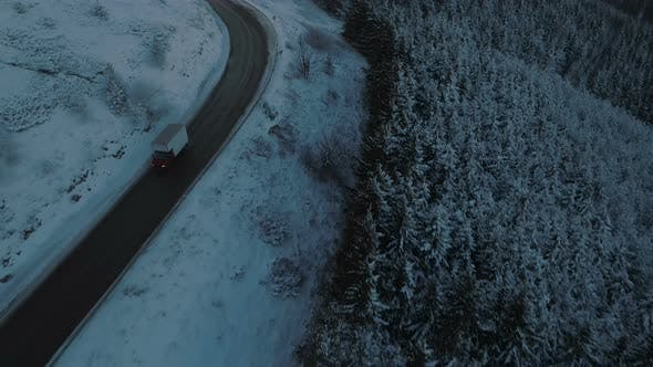 Transportation Truck Driving Slow on Slippery Winding Mountain Road During Winter