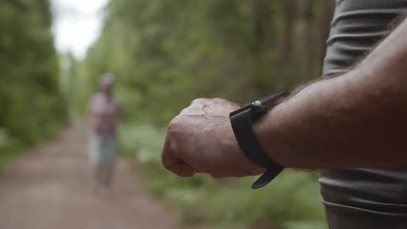 Unrecognizable Man Using Smartwatch during Training