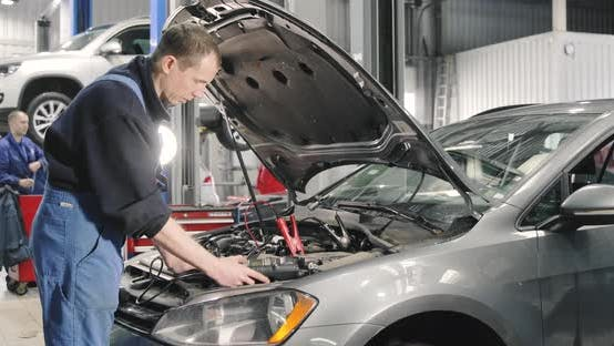Thumbnail for Mechanic Man Measuring Voltage On Car Battery In Auto Service. Car Maintenance