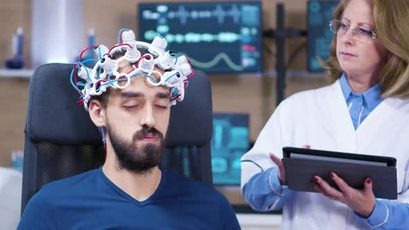 Male Patient with Eyes Closed While Doctor Checking Brain Activity