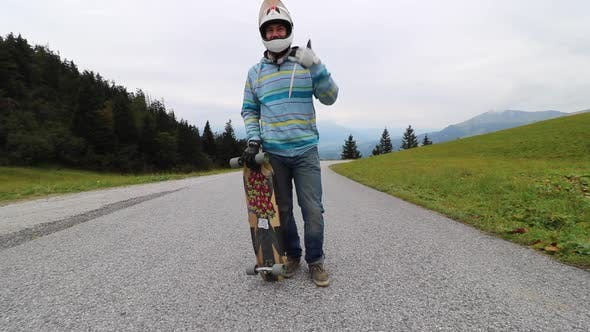 Thumbnail for A man downhill skateboarding on a mountain road