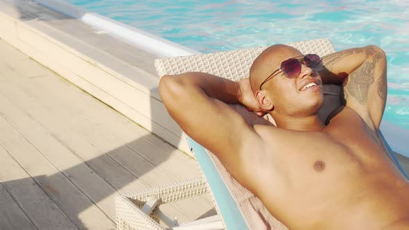 Thumbnail for Sliding Shot of a Handsome African Man Sunbathing By the Pool