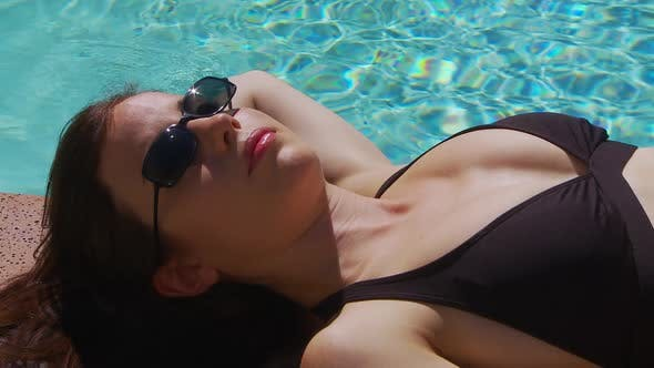 Thumbnail for Young woman sunbathing by side of pool