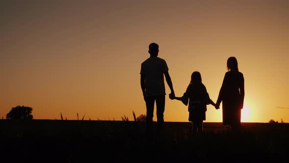 Thumbnail for Young Family with a Child Admiring the Sunset in the Field, Holding Hands