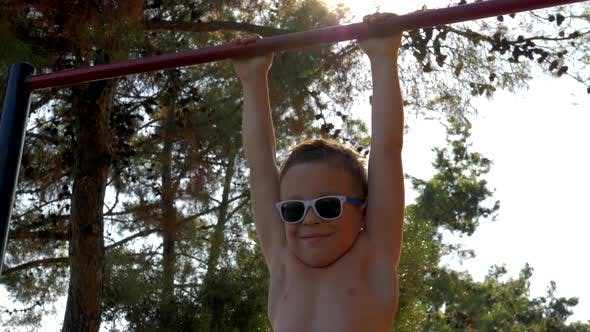 Child on pull-up bar at sports ground outdoor