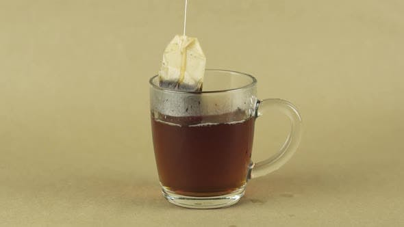 Thumbnail for Black Tea Bag Lifting and Dropping Into Glass Transparent Mug To Brew Tea Isolated on Beige