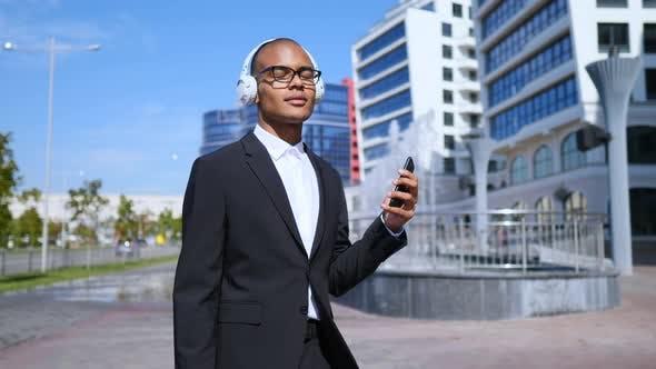 Thumbnail for Dancing Businessman Using Smartphone In Wireless Headphones