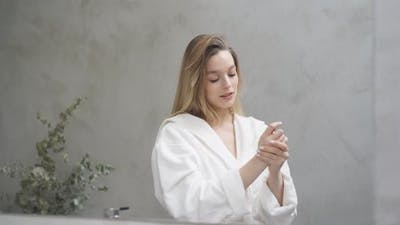 Goodlooking Woman in Bathrobe Looking at Mirror in the Morning