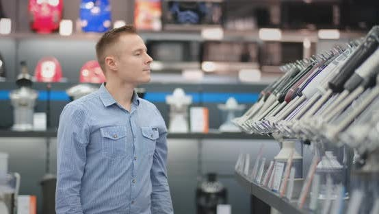 Thumbnail for A Young Man in a Shirt Chooses a Blender for His Kitchen in a Consumer Electronics Store