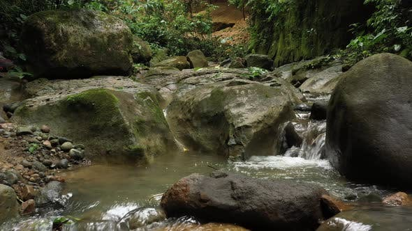 Flying above a stream in the tropics showing the water flowing