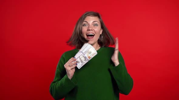 Thumbnail for Satisfied Happy Excited Woman Showing Money - U.S. Dollars Banknotes on Red