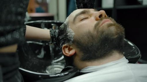 Closeup of a Head Wash in a Barber Shop with Gloves on