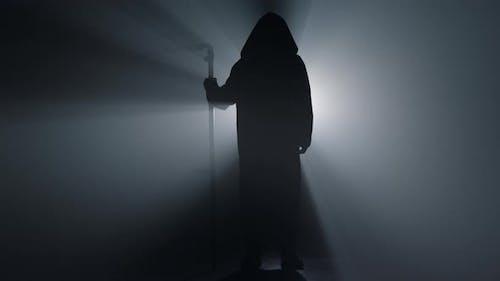 Silhouette Scary Scytheman Standing in Dark Background
