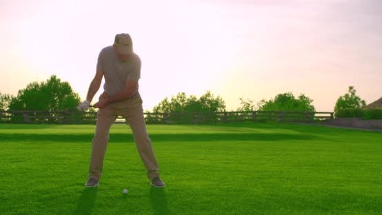 Thumbnail for Handsome Older Golfer Swinging and Hitting Golf Ball on Beautiful Course at Sunset