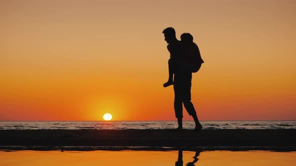 Thumbnail for A Young Man Plays with a Child, Carries Him on His Shoulders on the Beach