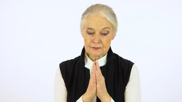 Thumbnail for An Elderly Woman Prays with Hands Clasped Together