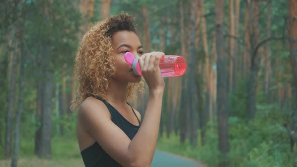 Thumbnail for Black Woman Drinking From Pink Bottle. Portrait of Black Young Woman Taking Break While Jogging