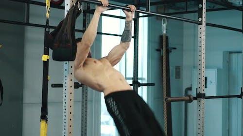 Strongman trainiert Bauchmuskeln auf Bar im Fitnessstudio
