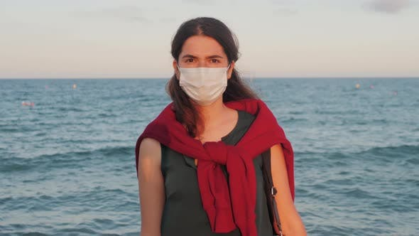 Tourist Woman in a Medical Face Mask on the Beach