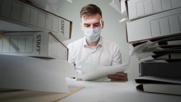 Tired Businessman Wearing Medical Protective Mask with Pile of Folders Working in Office Employee