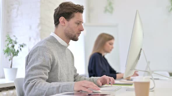 Cover Image for Focused Creative Man Working on Desktop in Modern Office